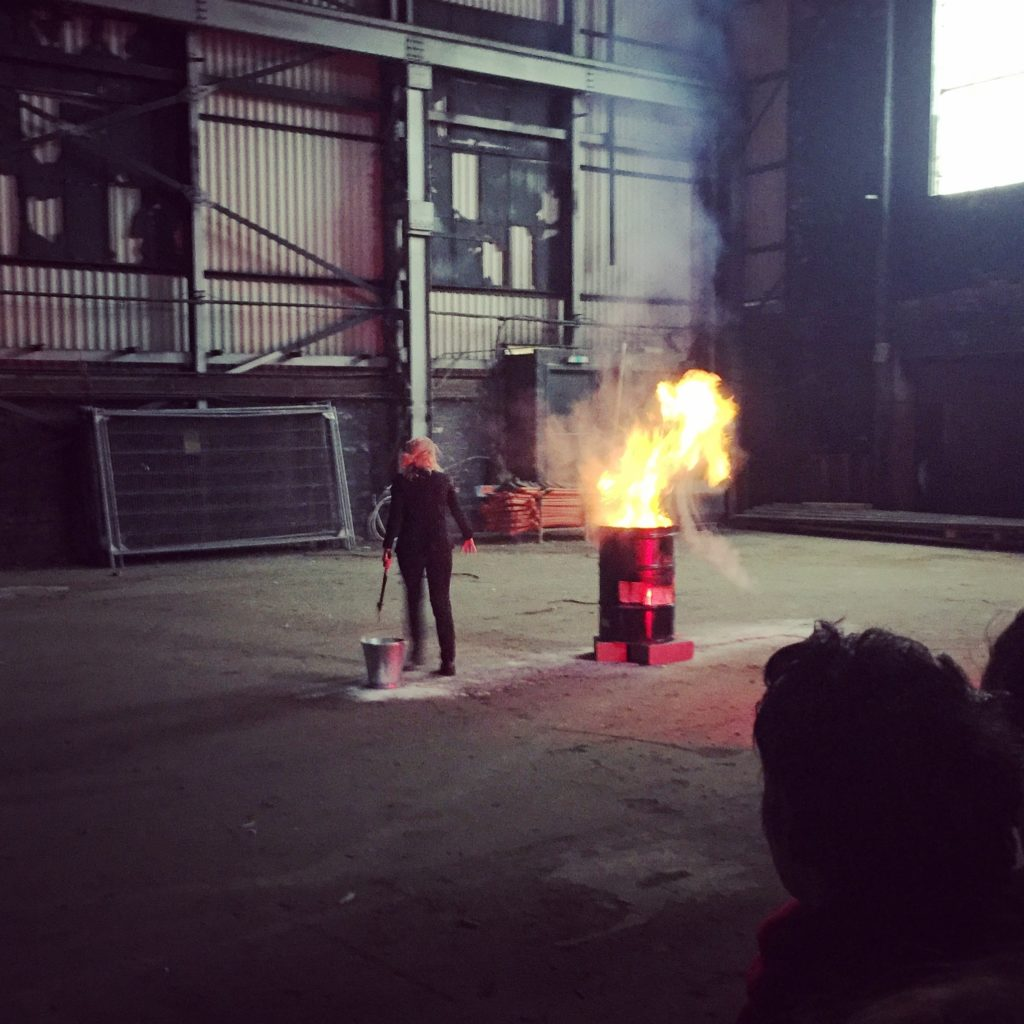 The artist FK Alexander holding an axe standing next to flaming barrel in a warehouse. She is standing on a bare concrete floor looking over her left shoulder.